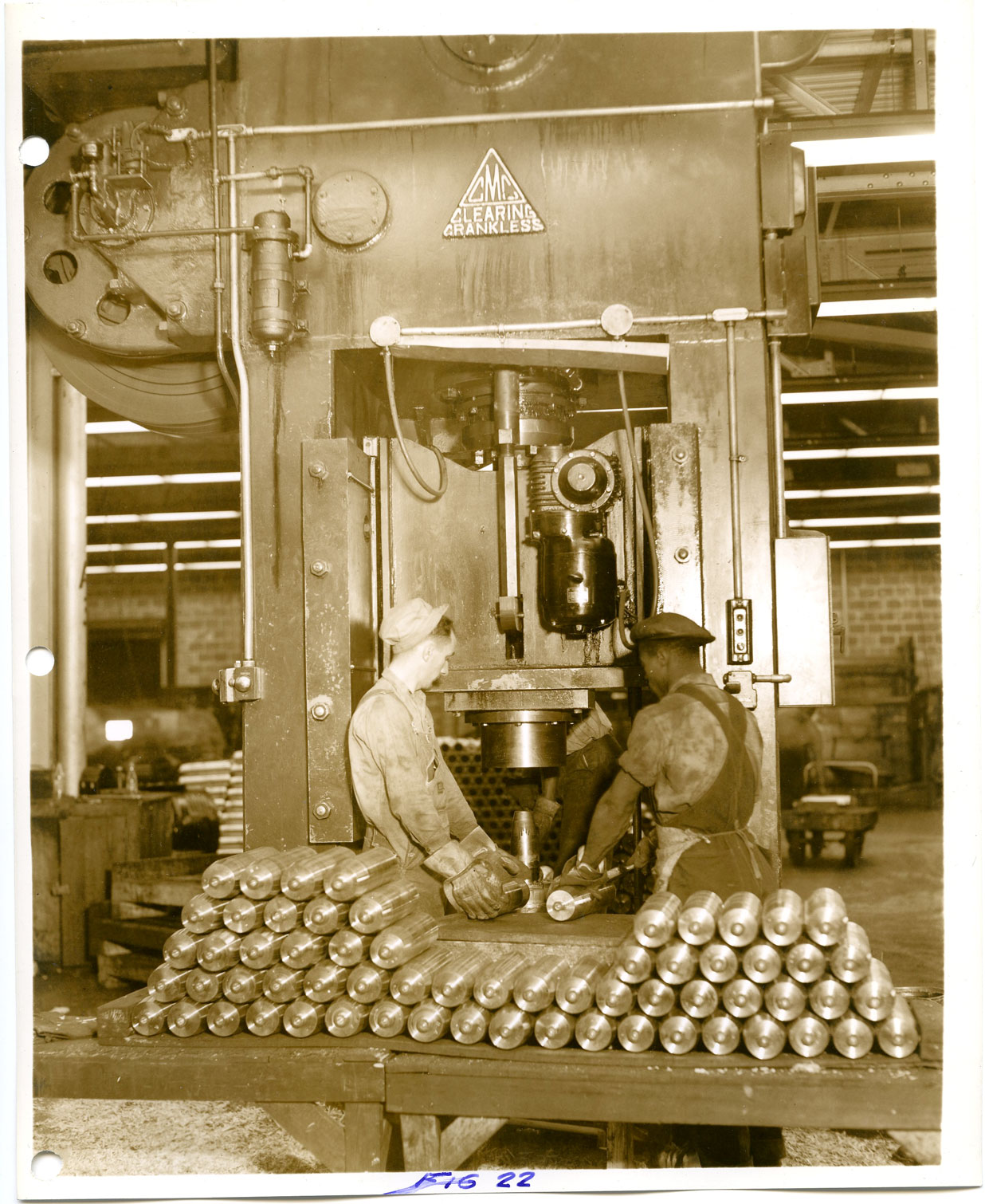 A white employee and a black employee work together at a machine press while manufacturing artillery shells.