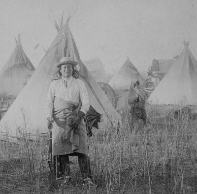 Man standing in front of tepees