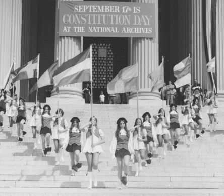 Students marching with flags on the steps of the National Archives