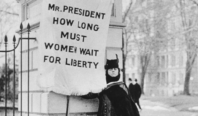 Woman at the White House holding a flag: Mr. President How Long Must Women Wait for Liberty