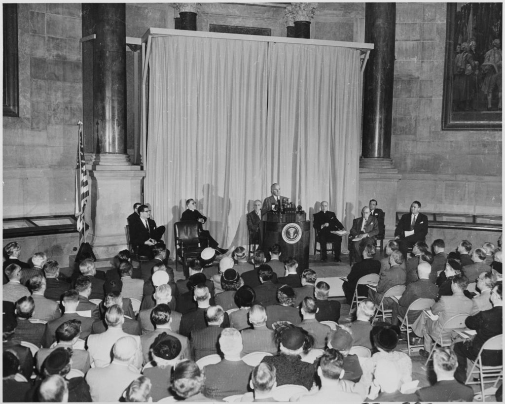 President Truman Giving a Speech at a Podium with a Crowd Watching